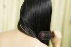Cura di capelli Primo piano di bei capelli di Hairbrushing della donna con la spazzola Ritratto della donna femminile sexy che sp immagini stock
