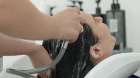 Cura di capelli professionale, lavante la testa del cliente in lavandino sotto la doccia nello studio di bellezza