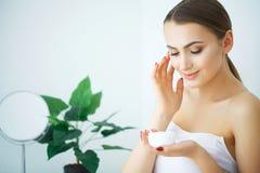 Cura di pelle di bellezza Bella donna che applica la crema di fronte cosmetica immagine stock