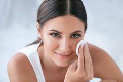 Cura di pelle del fronte Bella donna che rimuove trucco con il cuscinetto di cotone fotografia stock