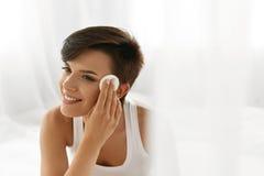 Cura di pelle di bellezza Donna che rimuove trucco del fronte facendo uso del cuscinetto di cotone Immagini Stock Libere da Diritti