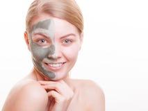Cura di pelle. Donna che applica la maschera dell'argilla sul fronte. Stazione termale. Fotografia Stock