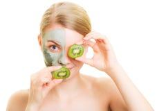 Cura di pelle. Donna nella maschera dell'argilla con il kiwi sul fronte immagine stock libera da diritti