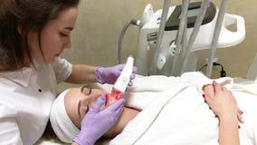 Cura di pelle La donna nel salone di cosmetologia ottiene il massaggio di GPL sul suo fronte stock footage