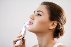 Cura di pelle Ritratto laterale della donna fresca in buona salute affascinante con trucco naturale facendo uso del massaggiatore Fotografie Stock
