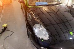 Cura e manutenzione di un'automobile nera alla stazione dopo avere lavato fotografia stock libera da diritti