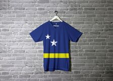 Curacao flag on shirt and hanging on the wall with brick pattern wallpaper stock photo