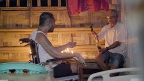 Curador hereditario que hace el ritual mágico para curar al hombre enfermo en silla de ruedas en tradiciones asiáticas Preparació almacen de video