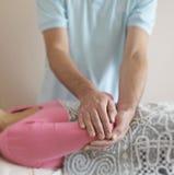 Curandeiro masculino que trabalha no cotovelo do paciente Imagem de Stock