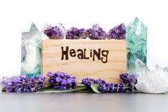 Curando - palabra quemada en madera con los cristales púrpuras de las flores, de la amatista, del fluorito y de cuarzo de la lava imagen de archivo