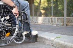 Curb. Man on a wheelchair who came to a bareer Stock Photos