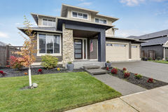 Curb appeal of brand-new home in brown and beige colors. Curb appeal of brand- home in brown and beige colors with two garages and concrete driveway. Northwest Stock Images