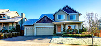 Curb appeal design idea. Pretty siding house with colomn porch  and attached garage. The green lawn with flower bed and trimmed hedges Royalty Free Stock Image
