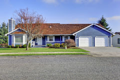Curb appeal one level American house with blue and white trim. And wooden porch. Also two garage doors and driveway. Northwest, USA Royalty Free Stock Images