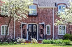 Curb appeal-Pretty upscale two story brick house with arched door and shtters and dogwood trees in bloom royalty free stock photos
