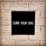 Curb Your Dog Sign. On a wall in New York City with a retro Instagram effect filter Stock Photos
