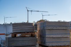 Curbs on several pallets, three cranes in background, blue sky royalty free stock images