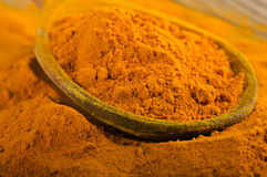 Curcuma powder on a wooden spoon Royalty Free Stock Images