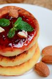 Curd cakes. Fried curd cakes with jam and almonds on a white plate. Traditional ukrainian dessert syrniki recipe. Vertical photo Royalty Free Stock Photography