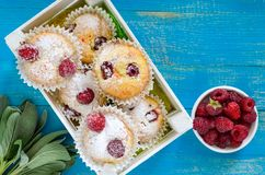 Curd cakes muffins with raspberries, decorated with powdered sugar. Serve in a white wooden box. Fresh raspberries in a ceramic bowl. Top view Stock Images