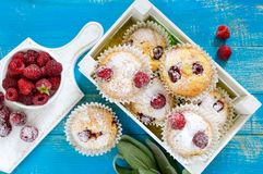 Curd cakes muffins with raspberries, decorated with powdered sugar. Serve in a white wooden box. Fresh raspberries in a ceramic bowl. Top view Royalty Free Stock Image