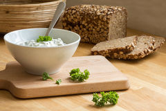 Curd cheese dip with herbs in a bowl and rustic bread in the bac Stock Image