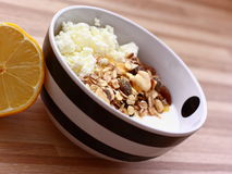 Curd cheese with muesli and lemon. A black and white bowl of a curd cheese and muesli Royalty Free Stock Images