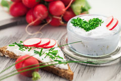 Curd with chives and bread. A bowl with curd and radish and a heart shaped chives decoration and brown bread Royalty Free Stock Photography