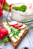 Curd with chives and bread. A bowl with curd and radish and a heart shaped chives decoration and brown bread Stock Photo
