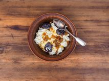 Curd in an earthenware bowl with the raisins, and dried apricots drizzled with honey on background of the table from the Royalty Free Stock Image