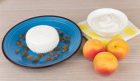 Curd and raisins in blue plate, sour cream and peaches Royalty Free Stock Photos
