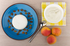 Curd and raisins in blue plate, sour cream and peaches Royalty Free Stock Images