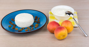 Curd and raisins in plate, sour cream, spoon and peaches Stock Image