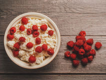 Curd with ripe fresh raspberries. In a bowl on wooden background, top view Stock Image