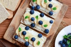 Cottage cheese, bananas and berries sandwiches with crisp bread on wooden board. Great cottage cheese sandwiches recipe. Closeup Royalty Free Stock Photos