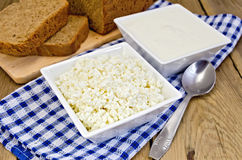 Curd and sour cream in bowls on board with bread Royalty Free Stock Images