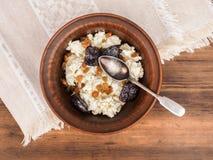 Curd w earthenware pucharze z rodzynkami i wysuszone morele na tle tablecloth i stół Zdrowy Zdjęcia Stock