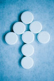 This is the cure 2. Closeup of an arrow made of tablets - blue tint royalty free stock image