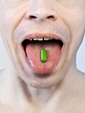 The cure. Closeup shot of man swallowing green pill Royalty Free Stock Photo