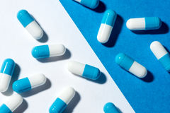 Cure capsule on a white and blue paper background Royalty Free Stock Image
