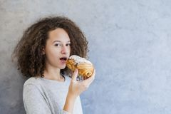 Cure curly hair girl eating croissant Royalty Free Stock Images
