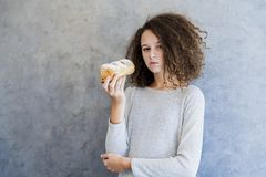 Cure curly hair girl eating croissant Royalty Free Stock Photo