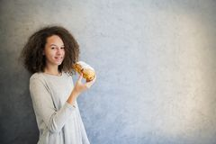 Cure curly hair girl eating croissant against wall Royalty Free Stock Photo