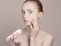 Cure della giovane donna per la pelle del fronte Immagine Stock