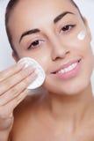 Cure della giovane donna per la pelle del fronte Fotografie Stock