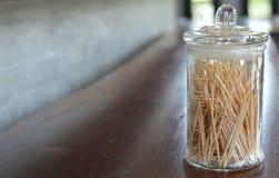 Cure-dents dans le pot en verre sur le bois photographie stock libre de droits