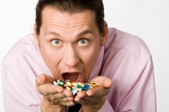 Cure of illness. Photo of frightened man with open mouth holding pills and eating them Royalty Free Stock Photos