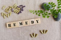 Remedy medicine concept. Cure remedy for diseases and illness - A conceptual photograph showing some green and purple pill capsules containing herbal medicines Stock Images
