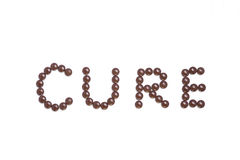 Cure written with brown pills royalty free stock photo