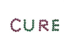 Cure written with purple and green pills Royalty Free Stock Image